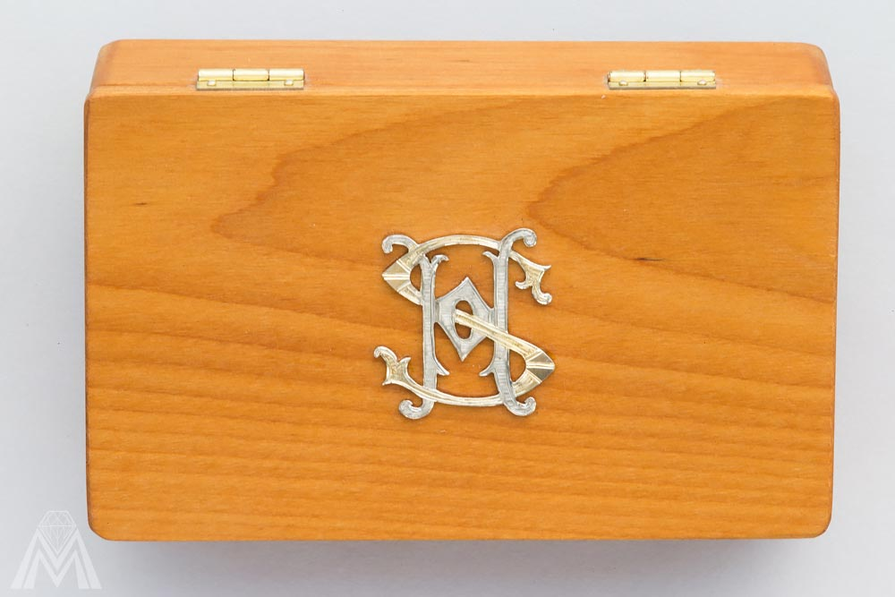 Puinen käyntikorttikotelo hopeisella monogrammilla.